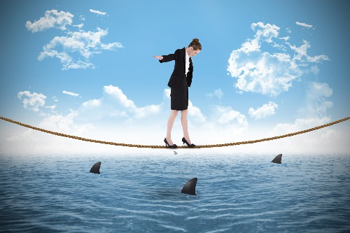 A woman HR Director walking a tightrope over shark infested waters